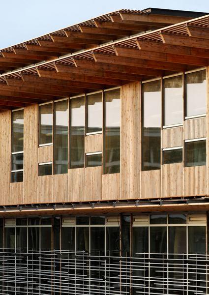 Centre névralgique du campus, l'Agora est un édifice plus massif, aux lignes plus géométriques. Perpendiculaire au premier bâtiment, elle est connectée à l'ensemble des cabanes nichées dans la forêt et représente le lien entre l'ancien et le nouveau campus.
