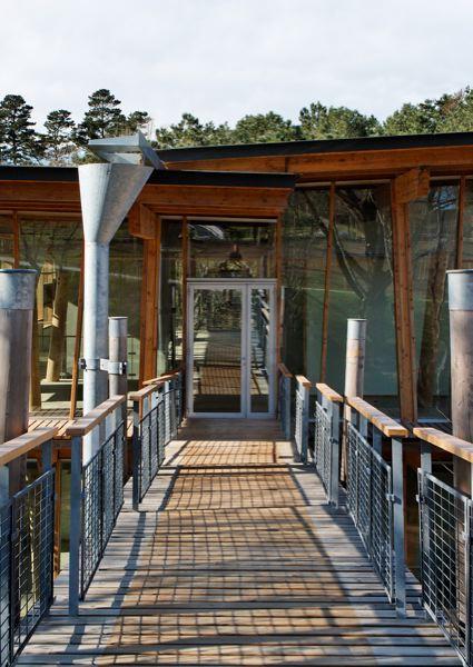 Cinq cabanes en bois accueillent chacune une marque ou un département. L'architecte a misé sur la clarté et la légèreté en privilégiant les armatures en bois et en verre, sur une base en béton à peine perceptible.