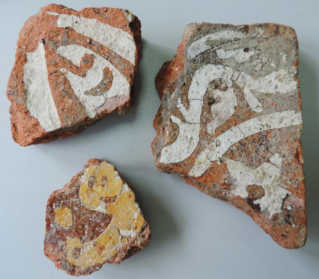 Fragments de carreaux de sol en terre cuite décorés de couleur jaune ou verte © Caroline Chauveau, Inrap