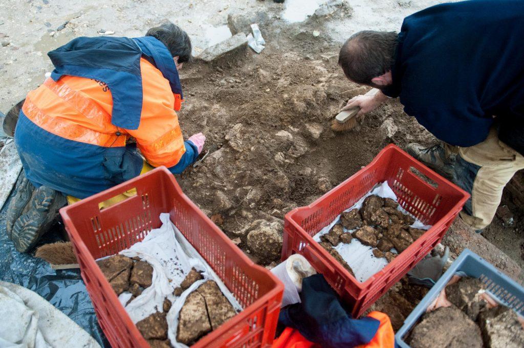 Les milliers de fragments de stucs rejetés en vrac dans une fosse sont minutieusement dégagés pour être prélevés un à un. © Antoine Morfaux, Inrap