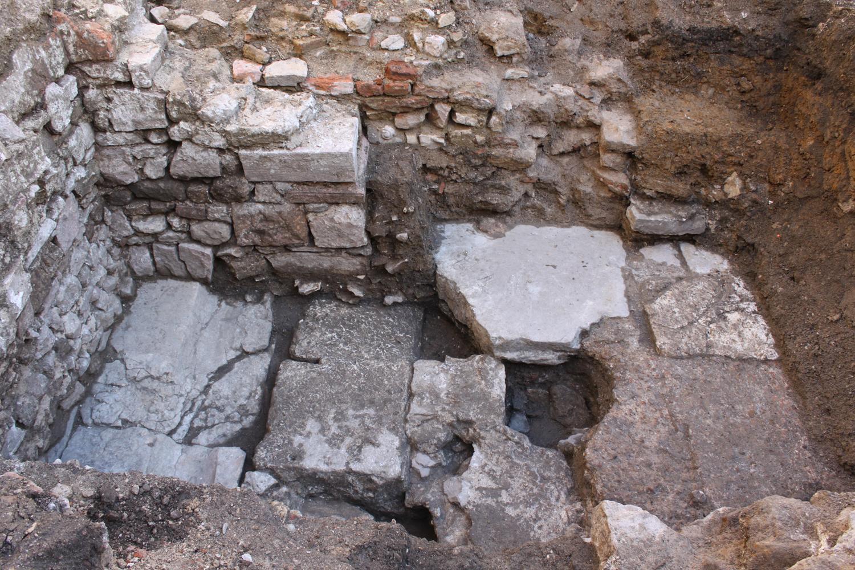 Caniveau donnant sur une rue (à gauche) et départ d'un sol en béton de tuileau d'une grande demeure aristocratique du début du Moyen Âge (à droite).